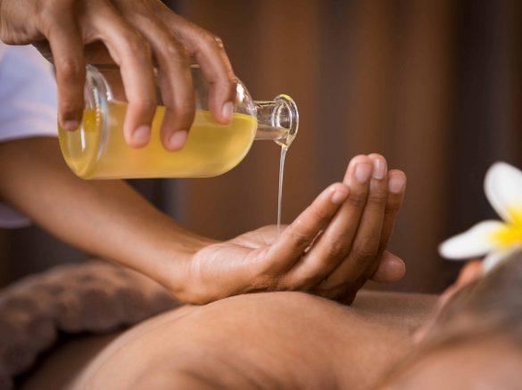 therapist-pouring-massage-oil-at-spa-GWM6LQV-min